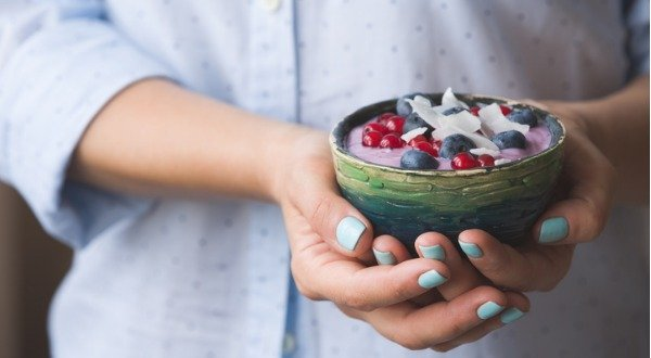 woman holding bowl of yogurt with probiotics