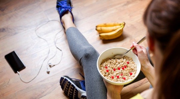 woman eating oatmeal in exercise clothes